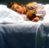 Little girl asleep in bed.